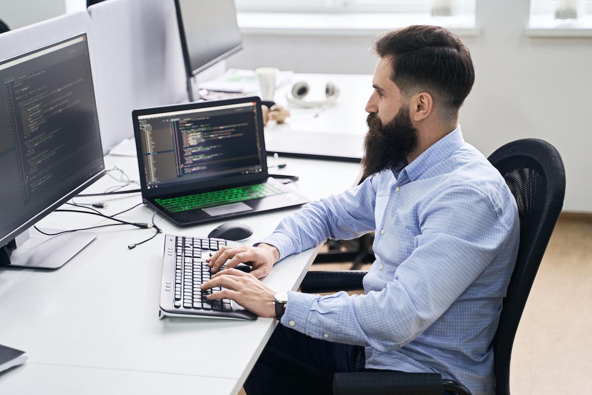An IT support employee running diagnostics on a laptop computer.